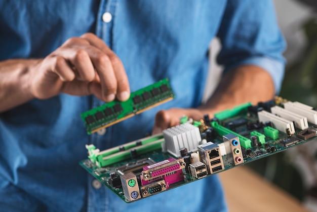 Mittlerer abschnitt des männlichen technikers ram in modernes pc-computermotherboard einsetzend