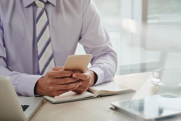 Mittlerer abschnitt des mannes e-mails auf smartphone überprüfend