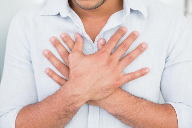 Mittlerer abschnitt des mannes mit schmerz in der brust
