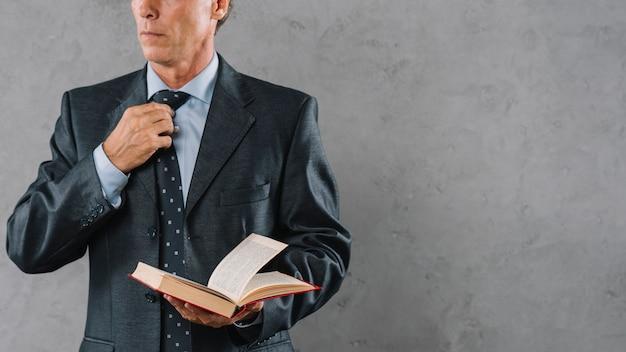 Mittlerer abschnitt des reifen männlichen rechtsanwalts, der buch im büro hält