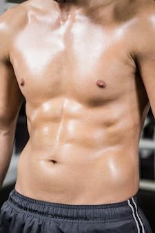 Mittlerer abschnitt des smirtless muskulösen mannes in der turnhalle