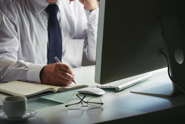 Mittlerer abschnitt des unerkennbaren mannes im formalwear, das anmerkungen am arbeitsplatzcomputer macht
