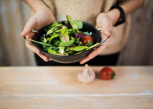 Mittlerer abschnitt einer frau, die frischen belaubten gemüsesalat im behälter über holztisch mit knoblauch und tomate hält