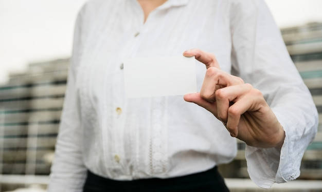 Mittlerer abschnitt einer geschäftsfrau, die leere visitenkarte zeigt