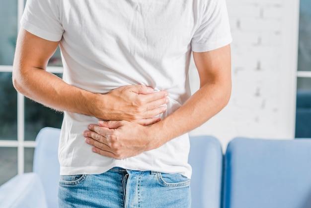 Mittlerer abschnitt einer mannholding, die schmerz im magen habend