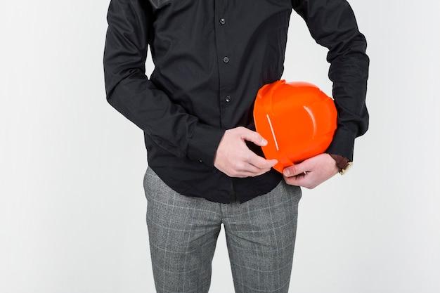 Mittlerer abschnitt eines architekten, der orange klemmbrett über weißem hintergrund hält