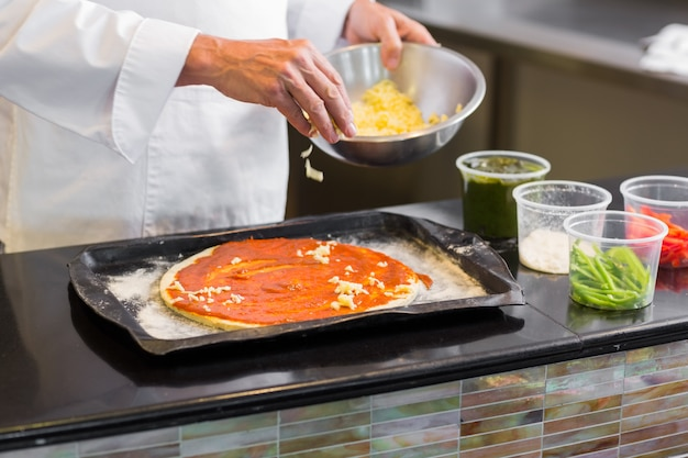 Mittlerer abschnitt eines chefs, der lebensmittel in der küche schmückt
