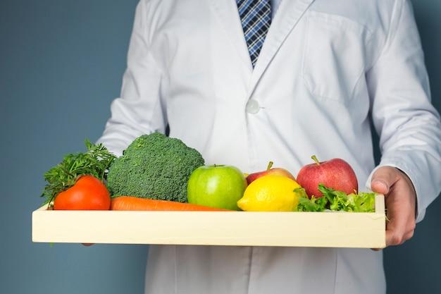 Mittlerer abschnitt eines doktors, der hölzernen behälter voll vom gesunden gemüse und von den früchten gegen grauen hintergrund hält