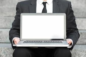 Mittlerer Abschnitt eines Geschäftsmannes, der einen offenen Laptop mit leerem weißem Bildschirm zeigt