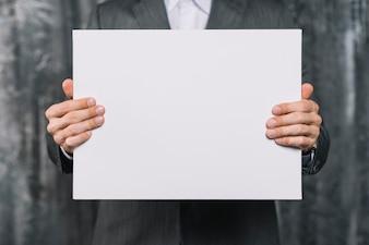 Mittlerer Abschnitt eines Geschäftsmannes, der leeres weißes Plakat zeigt
