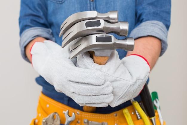 Mittlerer abschnitt eines heimwerkers, der hämmer mit toolbelt um taille hält
