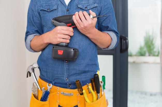 Mittlerer abschnitt eines heimwerkers mit bohrgerät und toolbelt