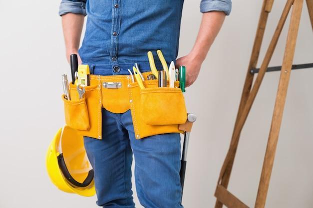 Mittlerer abschnitt eines heimwerkers mit toolbelt und schutzhelm