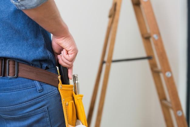 Mittlerer abschnitt eines heimwerkers mit toolbelt