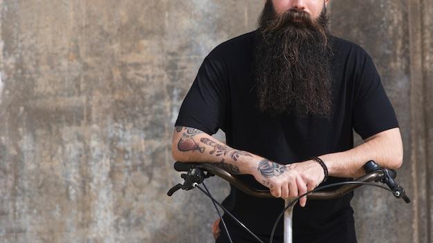 Mittlerer abschnitt eines mannes, der auf fahrrad gegen konkreten hintergrund sitzt