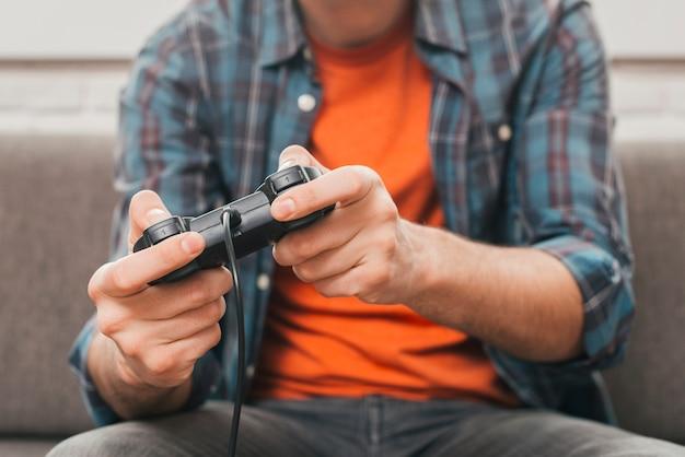 Mittlerer abschnitt eines mannes, der das videospiel mit steuerknüppel spielt