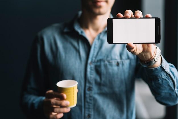 Mittlerer abschnitt eines mannes, der die wegwerfkaffeetasse zeigt mobiltelefonschirm hält