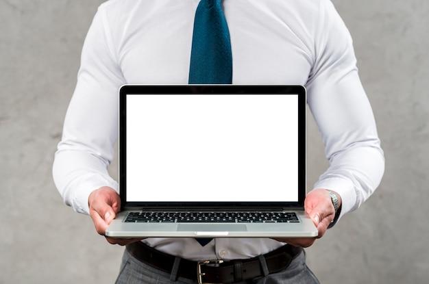 Mittlerer abschnitt eines mannes, der laptop mit leerem weißem schirm gegen graue wand hält