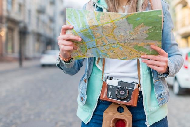 Mittlerer abschnitt eines weiblichen reisenden mit der kamera, die in der hand karte hält