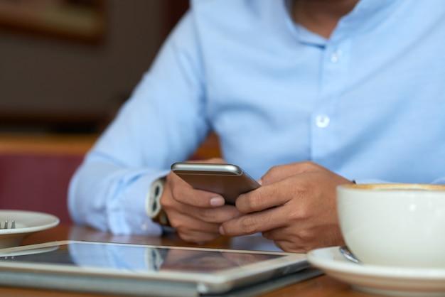 Mittlerer abschnitt von mannlesenachrichten online, kaffee trinkend