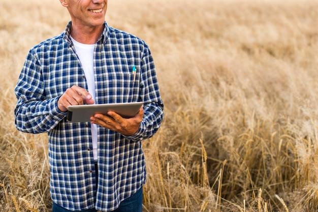 Mittlerer ansichtlandwirt mit einer tablette