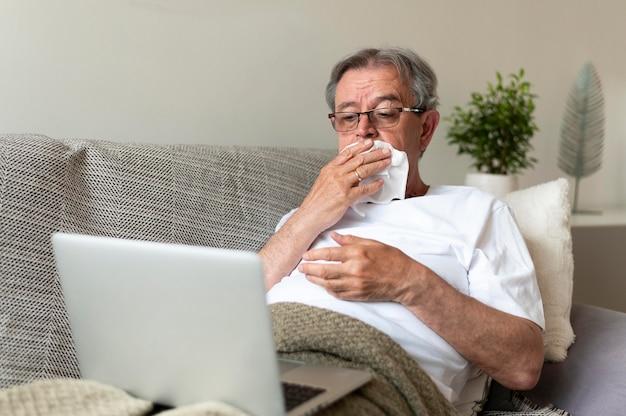 Mittlerer erschossener alter kranker mann auf der couch