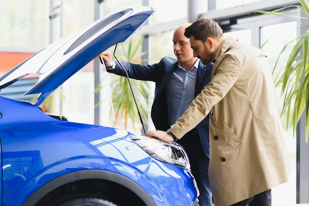 Mittlerer erwachsener autoverkäufer, der dem kunden im autohaus den motor zeigt