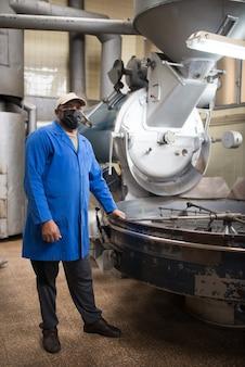 Mittlerer erwachsener kaffeeröster, der neben kaffeeröstmaschine steht. innenraum der kaffeeproduktionswerkstatt mit eingerichteter röstausrüstung