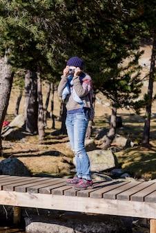Mittlerer erwachsener rucksacktourist mit pferdeschwanz, der im wald steht, während eine fotokamera verwendet wird, um ein shooting zu machen.