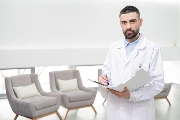Mittlerer erwachsener zahnarzt im weißmantel, der notizen im dokument macht, während er aufwirft