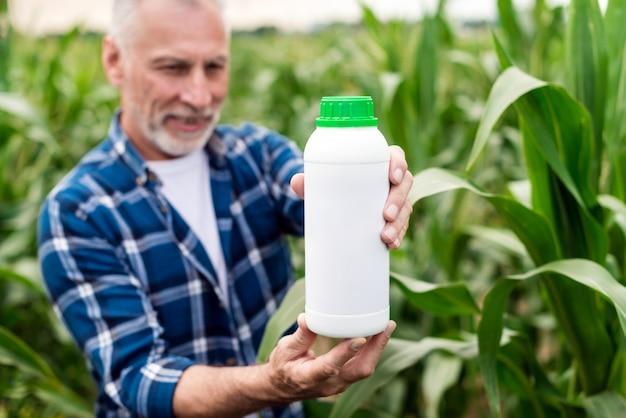 Mittlerer gealterter landwirt, der auf einem gebiet schaut auf einer flasche mit mineraldüngern in seinen händen steht.