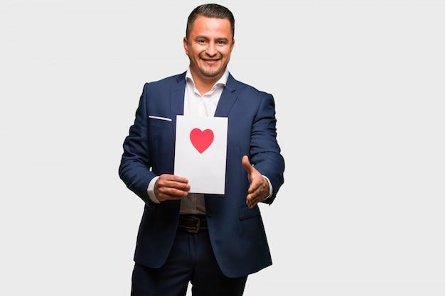 Mittlerer gealterter lateinischer mann, der den valentinsgrußtag feiert, um heraus jemanden zu grüßen