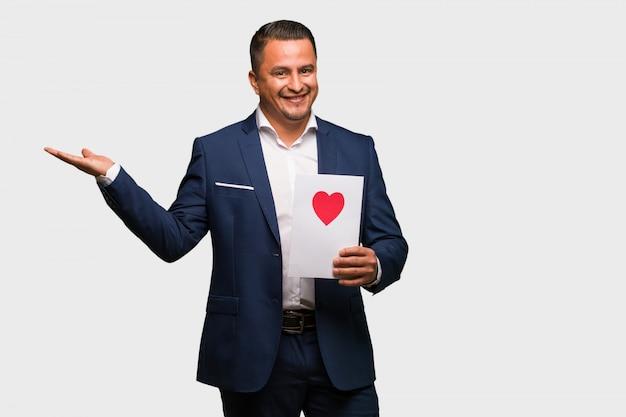 Mittlerer gealterter lateinischer mann, der den valentinsgrußtag hält etwas mit der hand feiert
