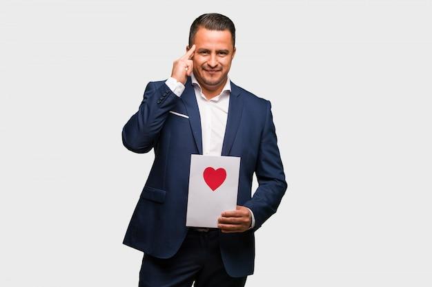 Mittlerer gealterter lateinischer mann, der den valentinsgrußtag tut, der eine konzentrationsgeste tut