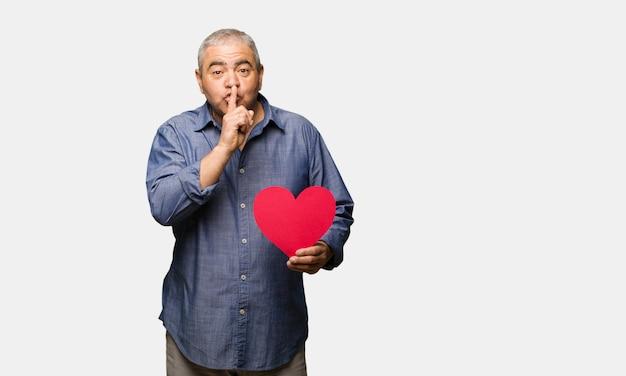 Mittlerer gealterter mann, der den valentinsgrußtag feiert, der ein geheimnis hält oder um ruhe bittet