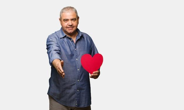 Mittlerer gealterter mann, der den valentinsgrußtag feiert, um jemanden zu grüßen