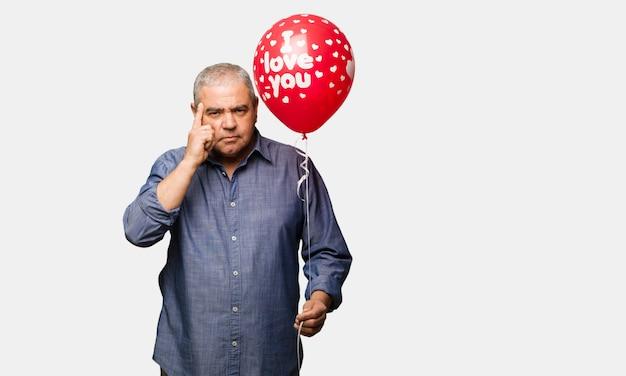 Mittlerer gealterter mann, der den valentinsgrußtag tut, der eine konzentrationsgeste tut