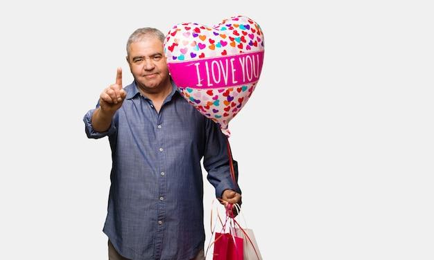 Mittlerer gealterter mann, der den valentinsgrußtag zeigt nummer eins feiert