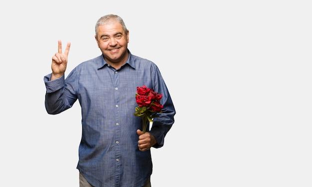 Mittlerer gealterter mann, der valentinsgrußtagespaß und glücklich tut, eine geste des sieges zu tun