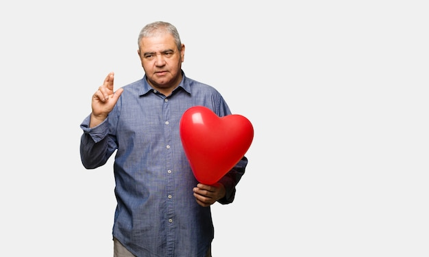 Mittlerer gealterter mann, der valentinsgrußtagesüberfahrtfinger für das haben von glück feiert