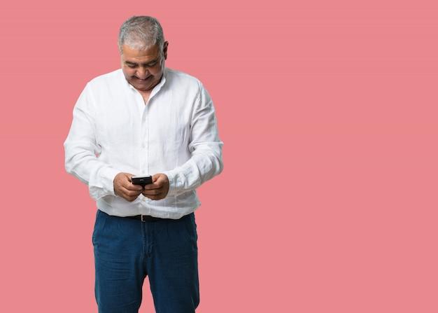 Mittlerer gealterter mann glücklich und entspannt, das mobile berührend, unter verwendung des internets und der sozialen netzwerke, positives gefühl der zukunft und der modernität