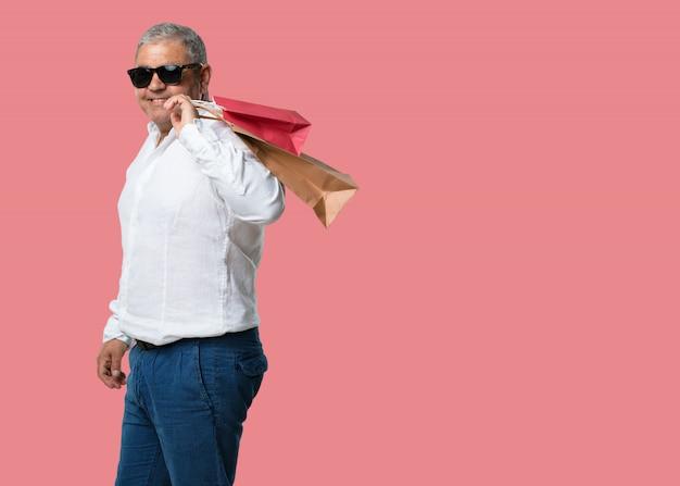 Mittlerer gealterter mann nett und lächeln, sehr aufgeregt, einkaufstaschen tragend