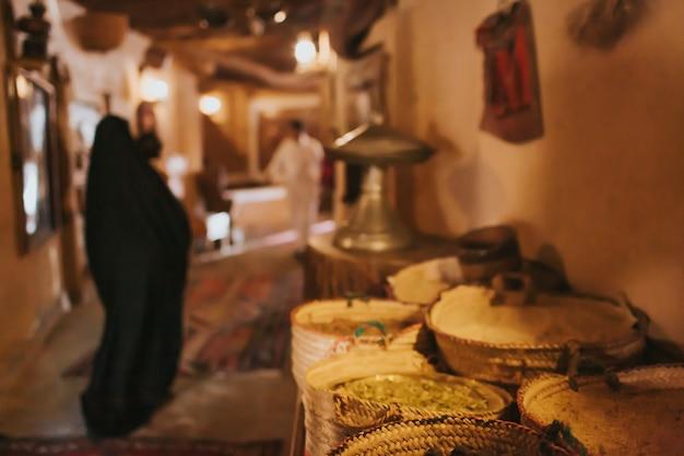 Mittlerer osten, alter basar. auf der theke stehen gewürze. verschwommene frau in schwarzer burka und abaya im hintergrund.