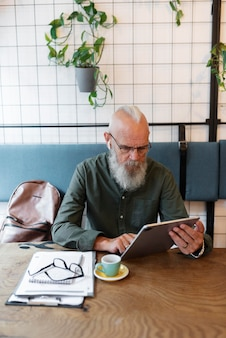 Mittlerer schuss älterer mann, der mit tablet studiert