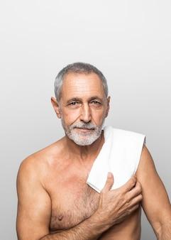 Mittlerer schuss älterer mann mit handtuch