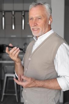 Mittlerer schuss älterer mann mit smartphone