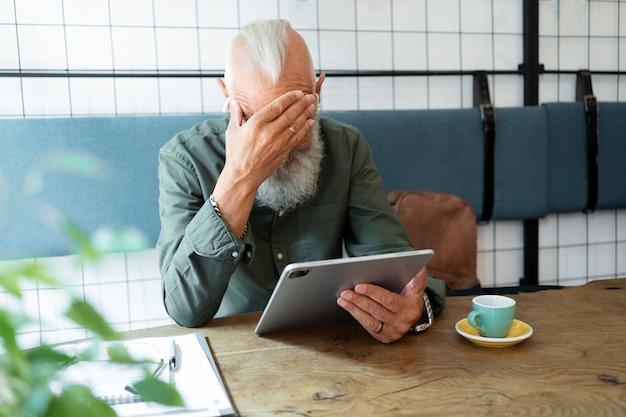 Mittlerer schuss älterer mann mit tablet