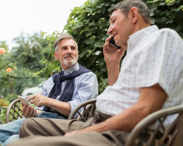 Mittlerer schuss alter mann, der am telefon spricht