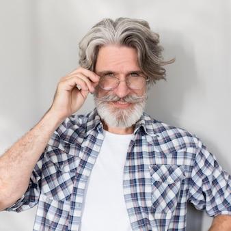 Mittlerer schuss alter mann, der brille hält
