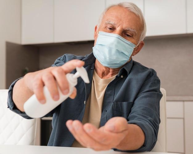 Mittlerer schuss alter mann, der desinfektionsmittel gießt